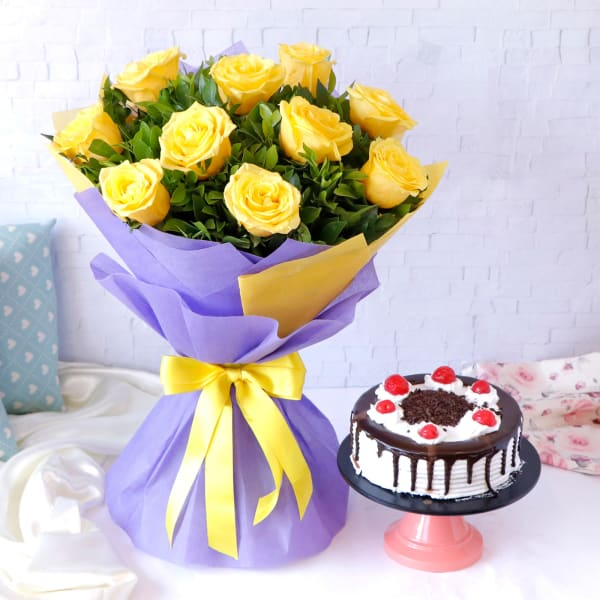 Yellow Roses Arranged in Blue Wrapping with Black Forest Cake (Half Kg)
