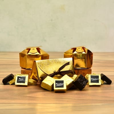 Strawberry-Hazelnut and Butter Scotch Chocolates in Golden Pouch With Ribbon