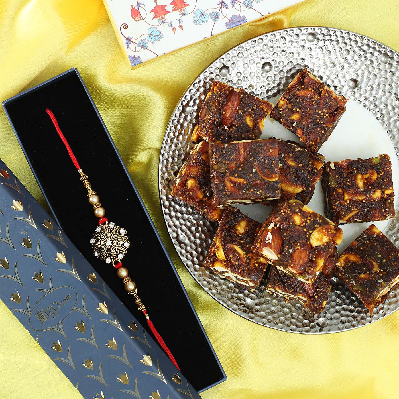 metallic-flower-dial-rakhi-with-sugar-free-anjeer-dry-fruit-barfi